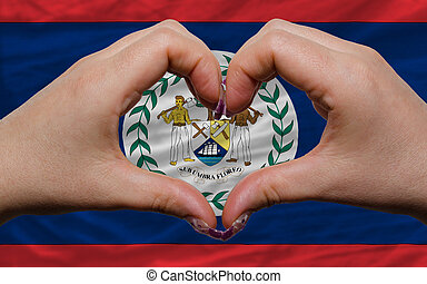 Gesture made by hands showing symbol of heart and love over national belize flag