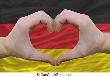 Gesture made by hands showing symbol of heart and love over germany flag