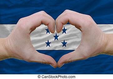Gesture made by hands showing symbol of heart and love over honduras flag