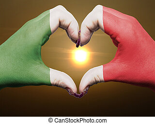 Gesture made by italy flag colored hands showing symbol of heart and love during sunrise