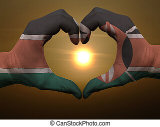 Gesture made by kenya flag colored hands showing symbol of heart and love during sunrise