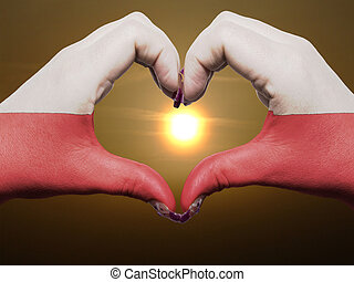 Gesture made by poland flag colored hands showing symbol of heart and love during sunrise