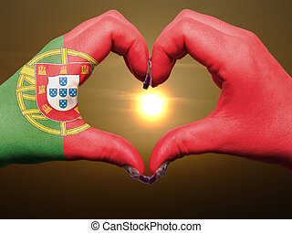 Gesture made by portugal flag colored hands showing symbol of heart and love during sunrise