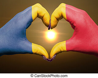 Gesture made by romania flag colored hands showing symbol of heart and love during sunrise