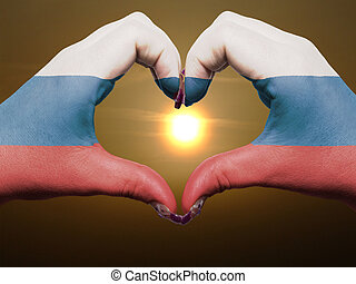 Gesture made by russia flag colored hands showing symbol of heart and love during sunrise
