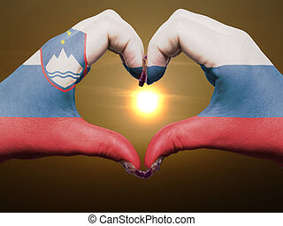 Gesture made by slovenia flag colored hands showing symbol of heart and love during sunrise