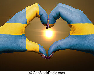 Gesture made by sweden flag colored hands showing symbol of heart and love during sunrise
