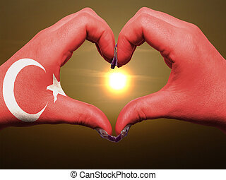 Gesture made by turkey flag colored hands showing symbol of heart and love during sunrise