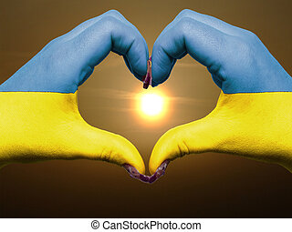 Gesture made by ukraine flag colored hands showing symbol of heart and love during sunrise