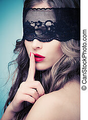 woman with black lace over eyes gesturing silence
