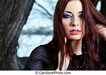 gesture - Shot of a gothic woman in a winter park. Fashion.