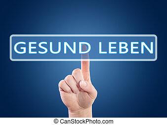 Gesund leben - german word for living well - hand pressing...