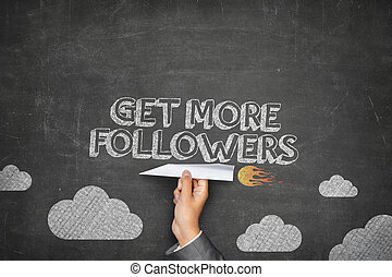 Get more followers concept on black blackboard with businessman hand holding paper plane