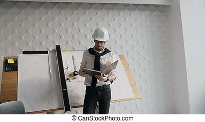 Get on the camera. Young Architect in a protective helmet standing on a construction site with a project folder in his hands