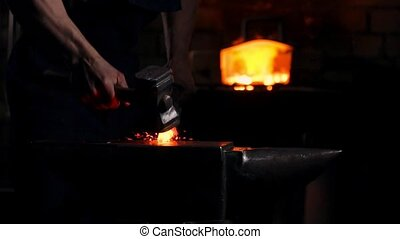 Get out of the furnace hot metal to make a sword war. Master of ancient art creates metal products. In slow motion blacksmiths hammer on red metal flying sparks