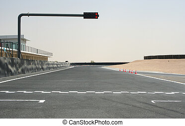 On the starting grid of a Kary track with RED stop lights.