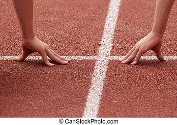Hands poised at the starting line of a race