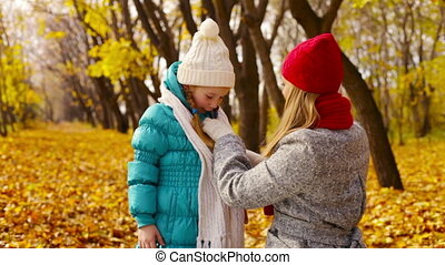 Get Warm - Caring mom putting a knitted scarf on her little...