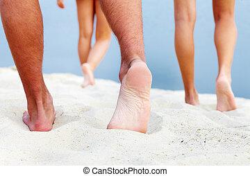 Soles of teenagers walking down sandy beach