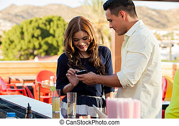 Pretty Hispanic brunette typing her phone number in a guy's cell phone
