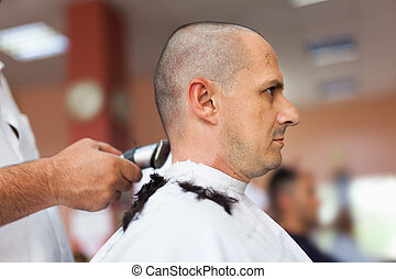 Getting a haircut - Caucasian man in a barber shop getting a...