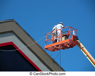 Getting A Raise - Men working in an industrial lift cage.