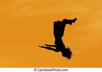 silhouette of a boy doing a back flip