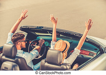 Getting away from it all. Top view of cheerful young couple keeping arms raised while riding in their white convertible