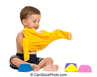 Getting dressed - A toddler is wearing his yellow shirt; ...