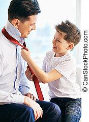 Getting dressed - Photo of happy boy tying necktie of his...