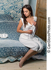 Young woman in authentic victorian bloomers and bodice is getting dressed in an antique bedroom with canopy bed