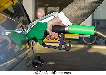 Getting gas - A man\'s hand filling up a car with gas or...