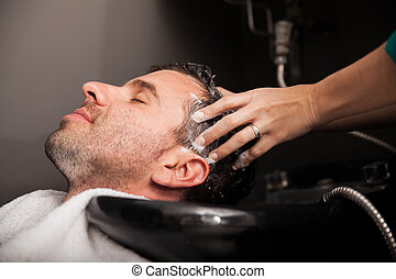Profile view of a young man getting his hair washed and his head massaged in a hair salon