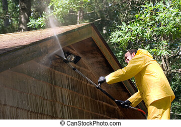 Getting It Clean - a man pressure washing a garage
