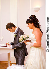 Getting married - Groom signing marriage papers focus on ...