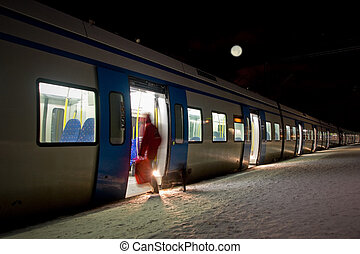 Getting on a train - woman getting on train in winter...
