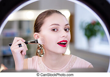 Pretty young woman looking at her face in the mirror