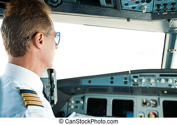 Getting ready to flight. Rear view of confident male pilot sitting in airplane cockpit