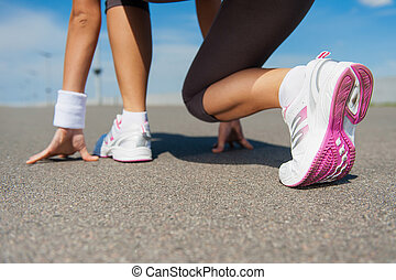 Getting ready to run. Close-up image of woman in sports...