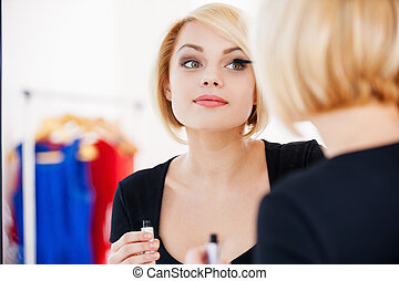 Getting ready to the night out. Beautiful young blond hair woman doing make-up and smiling while looking at the mirror