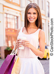 Getting refreshed after day shopping. Beautiful young smiling woman holding shopping bags and cup of hot drink while standing outdoors