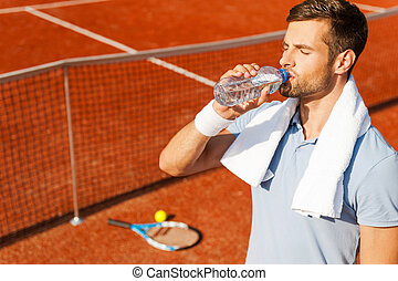 Getting refreshed after game. Thirsty young man in polo shirt and towel on shoulders drinking water while standing on tennis court
