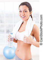Getting refreshed. Beautiful young woman in sports clothing holding a bottle with water and smiling at camera