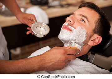 Getting shaved in a barber shop - Relaxed young man with...