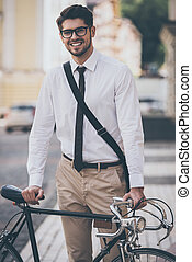 Getting to work. Cheerful young man in glasses looking at camera with smile and holding hand on his bicycle while standing outdoors