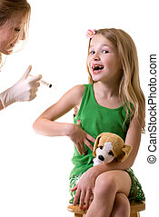 Female nurse or doctor holding a syringe with little girl child sitting looking at needle