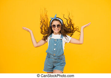Getting your hairstyle to last all day. Happy child with curly hairstyle flying on yellow background. Small cute girl smiling with long wavy hairstyle. Fashion look of hairstyle with glamorous curls