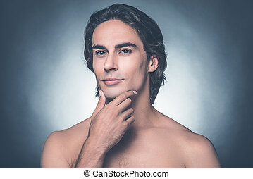 gevoel, fris, na, shaving., verticaal, van, mooi, jonge, shirtless, man, kijken naar van fototoestel, en, holdingshand, op, kin, terwijl, staand, tegen, grijze , achtergrond