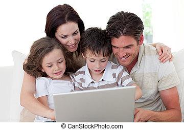 gezin, gebruik, een, draagbare computer, op de sofa