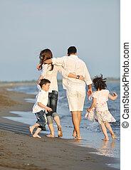 gezin, jonge, ondergaande zon , hebben vermaak, strand, vrolijke